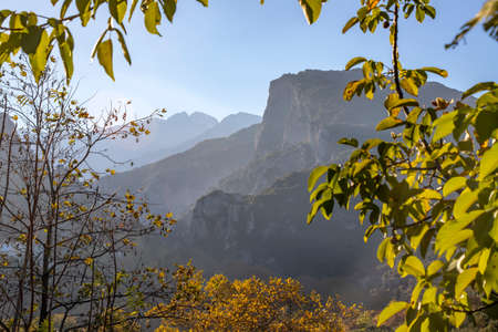 View of Mount Olympus in the fog in a frame of tree leaves. Litochoro Greece 스톡 콘텐츠