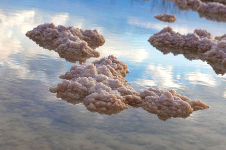 Crystals of mineral salts in the waters of the Dead Sea with the sky with clouds reflected in them. Seascape