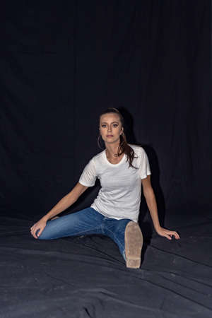 Girl in blue jeans and white t-shirt sitting on the floor on a Black background