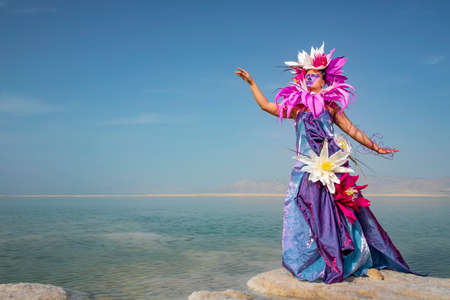 Young woman in a dress decorated with artificial flowers standing on a salty formation in the water of the dead sea against the sky and mountains.