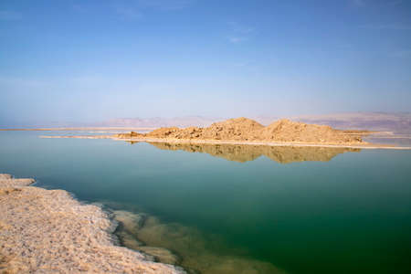 Reflection of hills in the salty water of the Dead Sea under which salt formations are visible 写真素材
