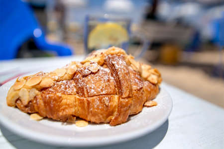 Croisson dusted with almonds and powdered sugar close-up on a blurred background. 写真素材