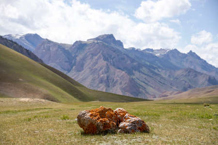 Boulder covered with lichen on a pasture against the blue sky with clouds and mountain ranges. Travel. Kyrgyzstan.