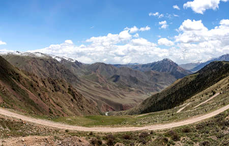View of the canyon from the pass 33 parrots - Teskey-Torpok. Mountain ranges with snow-capped peaks. Kyrgyzstan Travel
