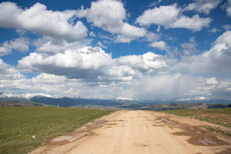 The road through the pasture with mountain ranges with snowy peaks on the horizon against a cloudy sky. Travel. Kyrgyzstan