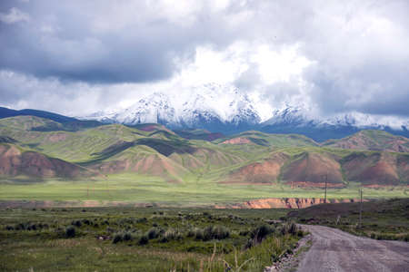 Gravel road between flowering fields and picturesque mountain ranges on the horizon. Kyrgyzstan Naryn region.