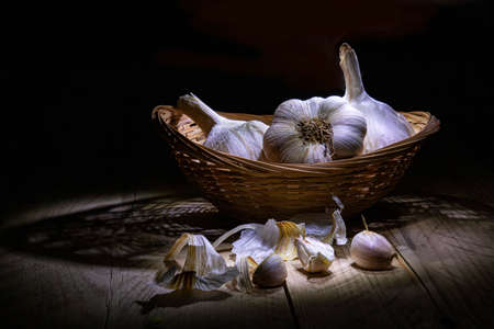 Still life on a black background. Garlic in a wicker wooden basket and on a wooden table in the backlight.