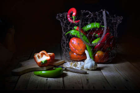 Still life on a black background. Red pepper, pumpkin, chilli pepper and garlic. Pepper halves lying on a chopping board.