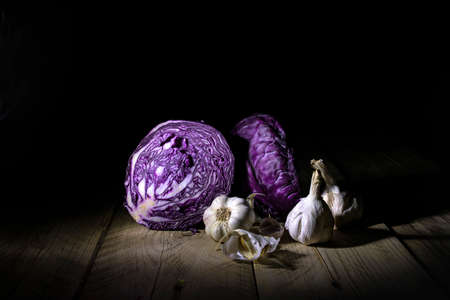 Red cabbage halves and ripe garlic in backlight lying on a wooden surface