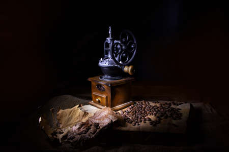Stylized vintage coffee grinder on a wooden table sprinkled with coffee beans and dry leaves.