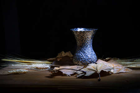 Still life against dark background. Metal vase standing on dry leaves and stalks of wheat.