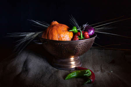 Still life on a black background. Orange pumpkin, red and green chilli peppers, purple onions, and dried wheat rings in a metal cup Reklamní fotografie