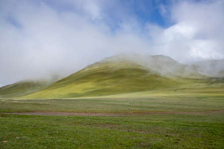 The road on the green field. Hills with descending fog. Kyrgyzstan