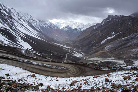 Top view of a serpentine mountain road between snow-covered hills.Kyrgyzstan Stock Photo