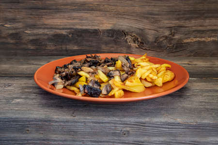 Plate of fried potatoes with porcini mushrooms on a wooden surface close-up Stock Photo