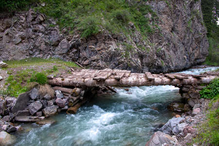 Mountain river with a wooden bridge between stony hills. Kyrgyzstan