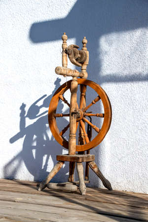 Wooden spinning wheel in the morning sun against a white wall closeup
