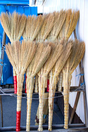Rows of handmade brooms in a rustic market close-up
