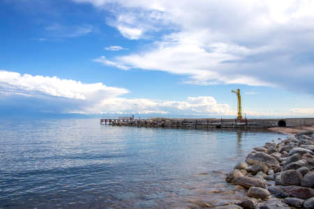 View of Issyk-Kul Lake, a mountain range with snow-capped peaks and a pier from a rocky beach. Kyrgyzstan Stock Photo