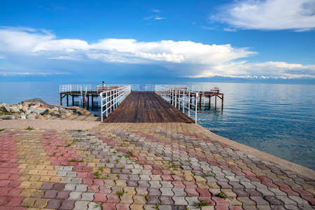 Pier on Issyk-Kul Lake on the background of a mountain range with snowy peaks and cloudy sky. Kyrgyzstan Stock Photo