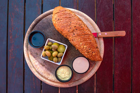 Top view on a round wooden board with bread, salted olives and cucumbers and various sauces.