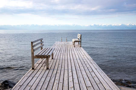 Pier with benches on Lake Issyk-Kul with a mountain range with snow-capped peaks on the horizon against a cloudy sky