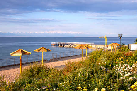 View of Issyk-Kul Lake, a beach with View of Issyk-Kul Lake, a beach with parasols and lawns with flowers and mountains on the horizon