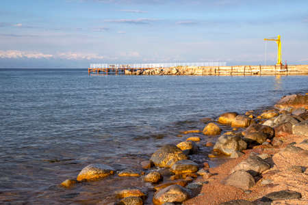 Side view of a pier on Issyk-Kul Lake with a mountain range with snowy peaks on the horizon against a cloudy sky