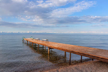 Pier with benches on Lake Issyk-Kul with a mountain range with snow-capped peaks on the horizon against a cloudy sky. Kyrgyzstan