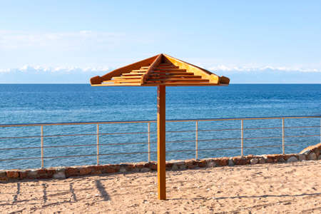 Parasol close-up on the beach of Lake Issyk-Kul with snow-capped mountains on the horizon. Kyrgyzstan Stock Photo