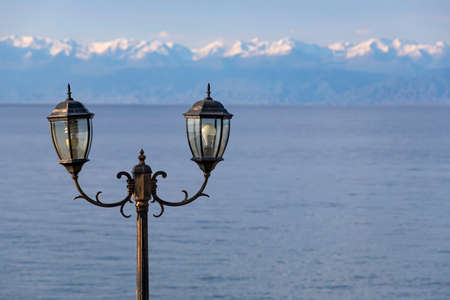 Electric lamp on the background of Lake Issyk-Kul with snowy mountains on the horizon. Kyrgyzstan