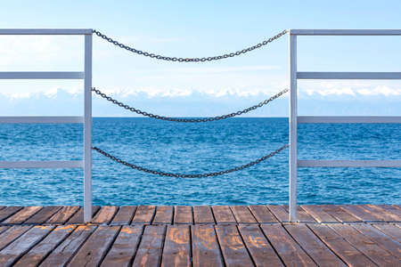 View of Issyk-Kul Lake and mountains with snow-capped peaks through the fence of a wooden pier. Kyrgyzstan