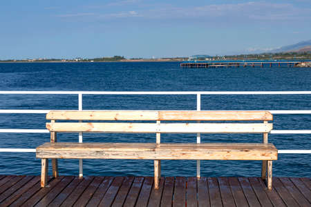 Bench on a wooden pier on Issyk-Kul Lake. Kyrgyzstan Stock Photo