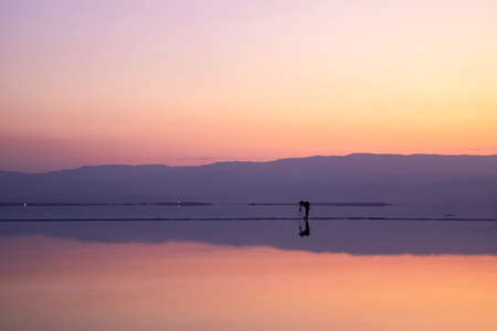 Photographer taking pictures of sunrise on the shore of the Dead Sea. Israel