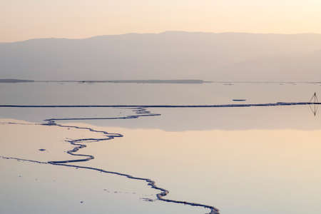 Reflection of the Jordanian mountains in the water of the Dead Sea with salt formations at dawn. Israel