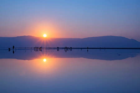 A group of photographers taking pictures of sunrise on the shore of the Dead Sea. Israel