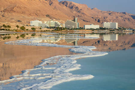 Reflection of mountains, hotels and palm trees in the water of the Dead Sea with salt formations. Israel
