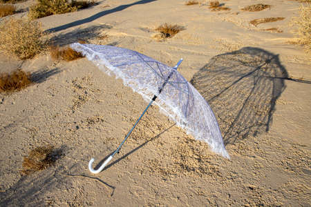 White sun umbrella casting a shadow on the dry surface of the earth in the Judean desert. Israel Stock Photo