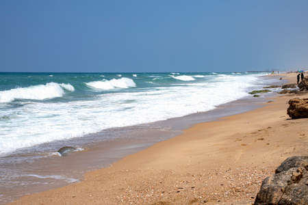Sea beach with stone formations and incident foam waves on the shore of Ashkelon National Park. Israel Stock Photo