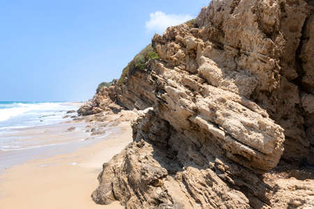 Sea beach With stone ledges and foamy waves on the shore of Ashkelon National Park. Israel