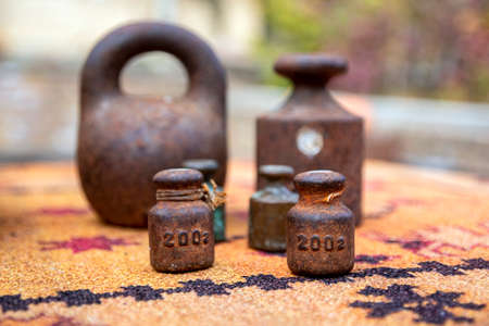 Closeup of rusty metal weights of various shapes and weights close up on a blurred background