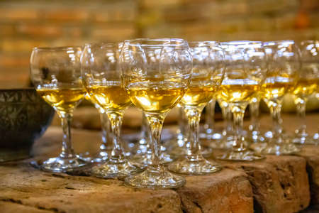 Rows of transparent glass goblets for wine filled with amber wine on a stone surface
