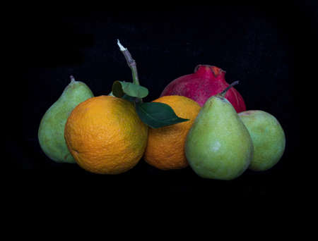 Still life. Pears, oranges and pomegranate on a black background close up