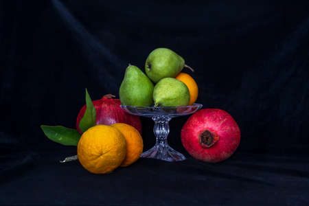 Still life. Pears in a glass vase, oranges and pomegranates on a black background close up 版權商用圖片