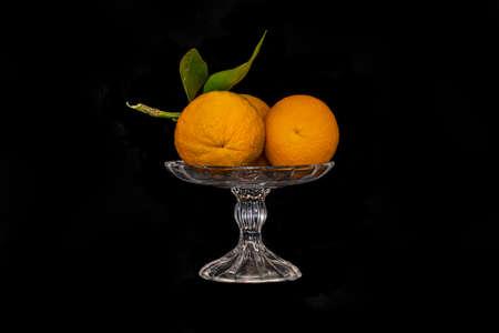 Still lifStill life. Ripe oranges in a glass vase on a black backgrounde close up