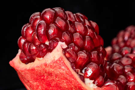 Still life. Juicy ripe opened pomegranate fruit with seeds close up
