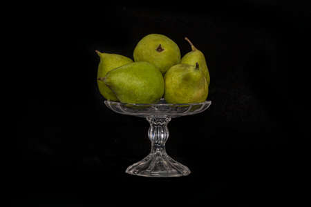 Still life. Ripe pears in a glass vase on a black background close up