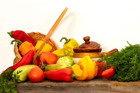 Still life of fresh vegetables on a wooden table against white background. Peppers, zucchini, tomatoes, dill.