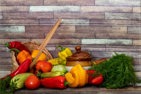 Still life of fresh vegetables on a wooden table against a brick wall. Peppers, zucchini, tomatoes, dill.