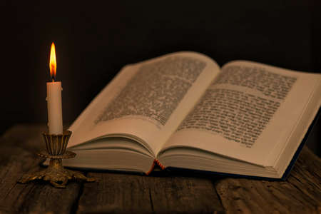 Open Torah and a burning candle in a candlestick on a wooden surface on a dark background close up
